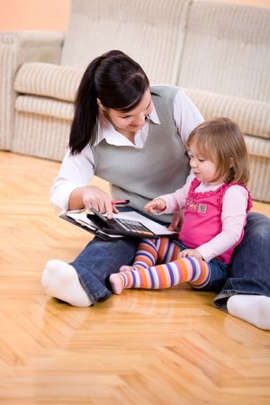 mother working at home with daughter photo