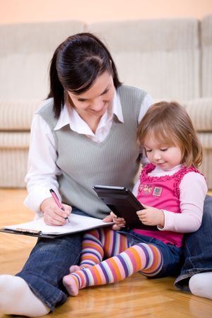 mother working at home with daughter Stock Photo