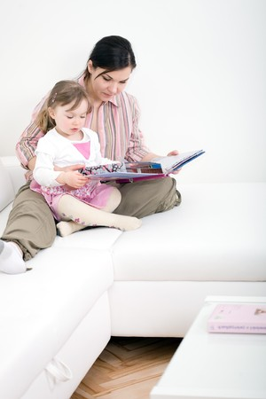 mother and daughter reading book at sofa photo