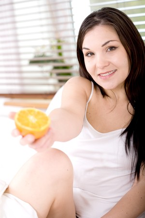 young happy woman eating fruit in bed photo