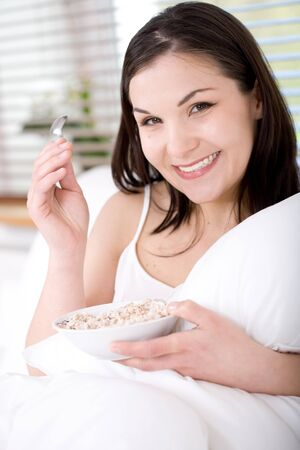 young happy brunette woman with corn flakes photo