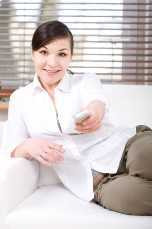 young happy woman sitting on sofa with remote control photo
