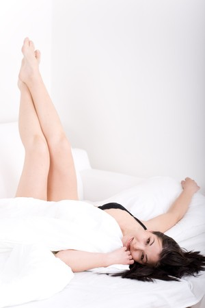 young adult woman relaxing in bed photo