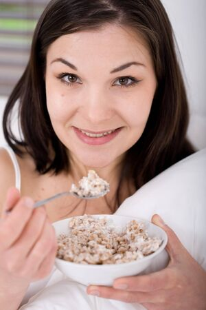young adult woman with corn flakes in bed photo