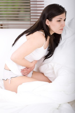 constipation: young adult brunette woman feeling pain in bed
