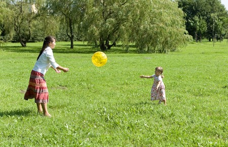 mother and daughter playing ball on meadow photo