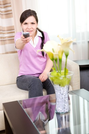 woman watching tv: young adult woman watching tv at home Stock Photo