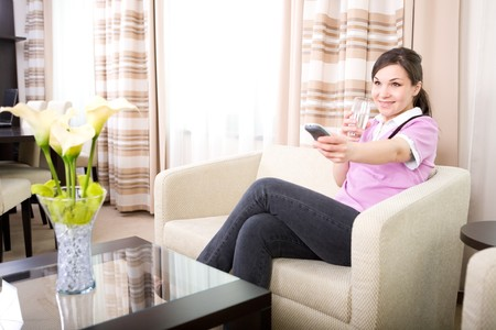 young adult woman watching tv at home Standard-Bild