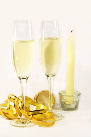 two flutes of champagne with canddle and golden ribbon photo