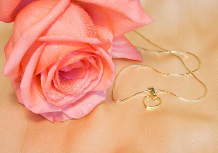 Golden chain with a heart and pink rose on silk background