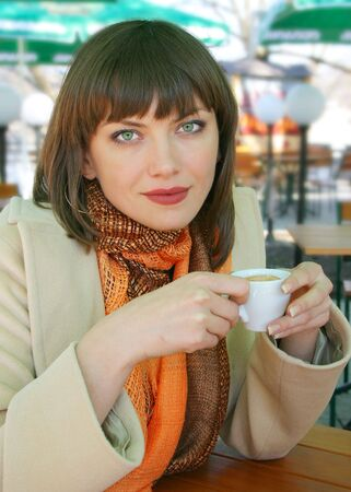 Young lady drinking coffee in a street cafe photo