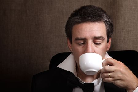 Picture of a man drinking coffe after celebration