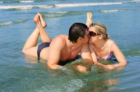 Picture of a young couple kissing on the beach  photo