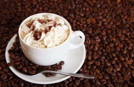 Cup of cappuccino over the coffee beans photo