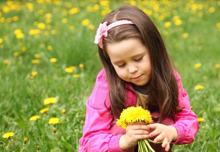 Little girl with dandelions in the meadow photo