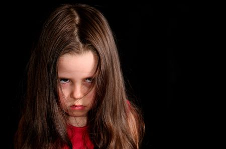Upset little girl over the black background