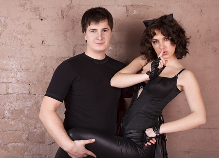 Young girl in the costume of cat woman flirting with the guy  photo