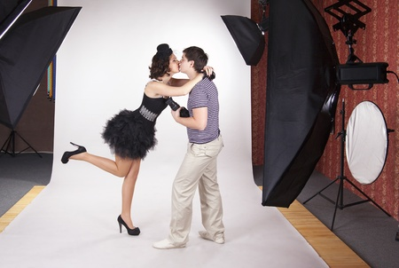 Young model kissing the photographer in the photostudio photo