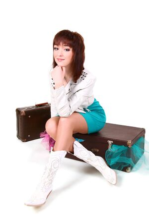 Young girl sitting on the old packed suitcase Stock Photo - 8892857