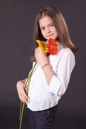 Beautiful girl with daisies over the gray background photo