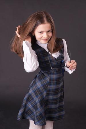 school uniform girl: Beautiful smiling schoolgirl over the gray background