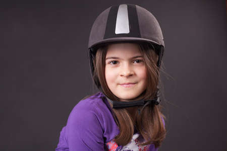 Beautiful girl in jockey cap over the gray background photo