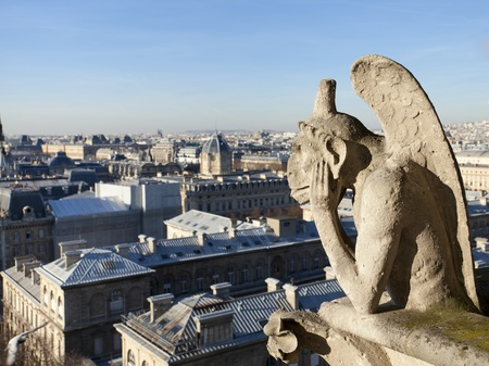 chimera: Notre Dame of Paris: Chimera overlooking the skyline of Paris at a sunset Stock Photo