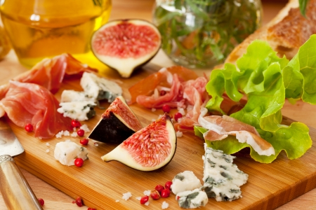 Ham, cheese and figs on the wooden board photo