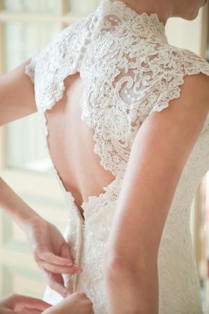 bröllop: Brud sätta på sin vita brudklänning Stockfoto