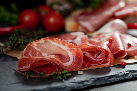 Ham , cherry tomatoes, red pepper and herbs on black stone slate board.