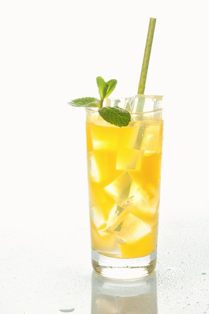 Glass of cold refreshing orange drink with ice and mint Stock Photo