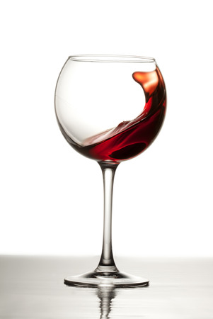 Red wine splashes out of a glass making waves in the glass