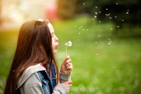 Cute teenage girl in the summer garden blowing a dandelion photo