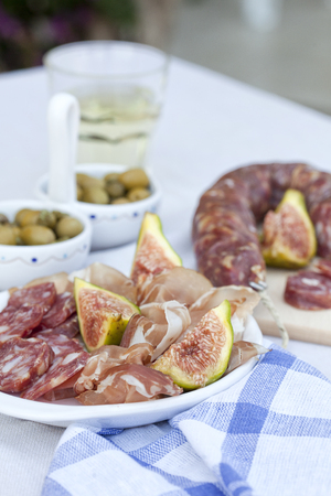 traditional mediterrenian meat appetizers with olives, figs and white wine