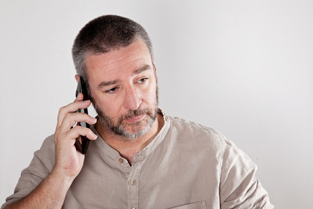 Mature man talking over the cell phone Imagens