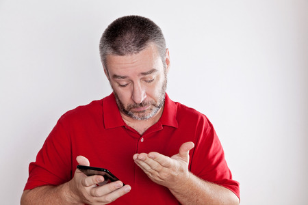 Mature man searching for information in his cell phone