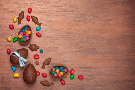 Flat lay Easter composition with chocolate eggs on color wooden background, space for text Stock Photo