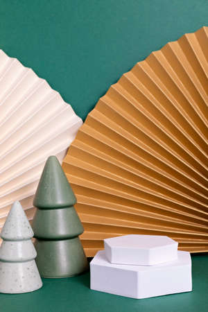 Podium, stand, platform for product presentation.Abstract background made of paper fans and Christmas decoration.Mockup for branding and packaging presentation