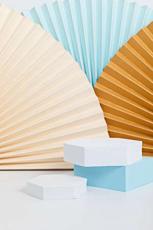 Podium, stand, platform for product presentation. Abstract background made of paper fans. Mockup for branding and packaging presentation Archivio Fotografico