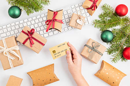 Online christmas shopping concept with gift boxes, keyboard and golden credit card. Top view, flat lay, mock up Stock Photo