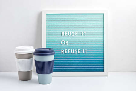 Reusable coffee cup and letterboard with text reuse it or refuse it. Zero waste sustainable lifestyle. Eco friendly habbits for take away coffee