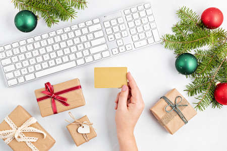 Online christmas shopping concept with gift boxes, keyboard and mockup of golden credit card. Top view, flat lay, mock up Stock Photo