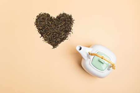 White ceramic tea pot with dry green tea leaves in heart shape on beige background. Eco friendly organic brand concept