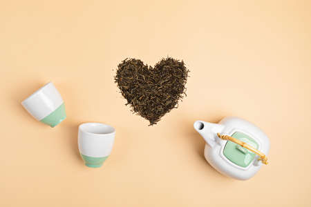 White ceramic tea pot with dry green tea leaves in heart shape on beige background. Eco friendly organic brand concept. Branding mockup