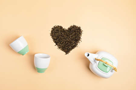 White ceramic tea pot with dry green tea leaves in heart shape on beige background. Eco friendly organic brand concept. Branding mockup. Flat lay