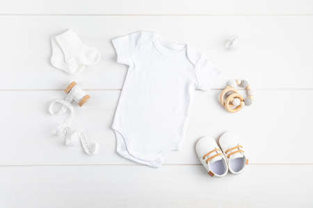 Mockup of white infant bodysuit made of organic cotton with eco friendly baby accessories Archivio Fotografico