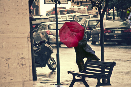 windy city: People rushing on the windy rainy street. Red Umbrella Stock Photo