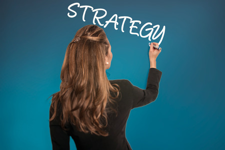 Businesswoman writing a Strategy on a wall - Stock Image photo