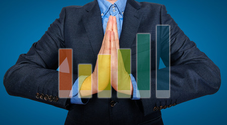 Young Man Businessman praying and Wishing Hard. Graph in front. Blue background - Stock Image photo