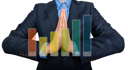 Young Man Businessman praying and Wishing Hard. Graph in front. White background - Stock Image photo